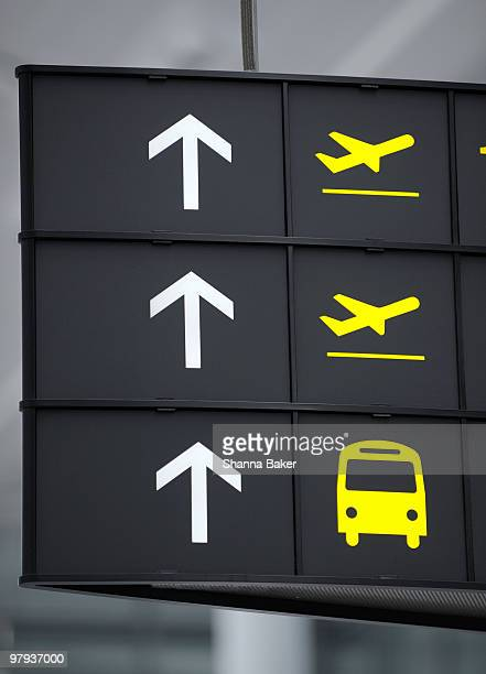 Airport sign showing arrows and airplanes