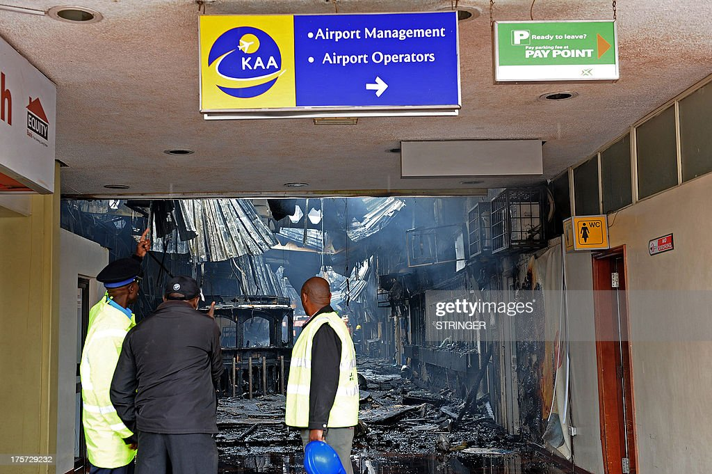 Airport staff look at the debris after a fire damaged a terminal at the Jomo Kenyatta international airport in Nairobi on August 7, 2013. A massive fire shut down Nairobi's international airport on Wednesday with flights diverted to regional cities as firefighters battled to put out the blaze in east Africa's biggest transport hub. Dramatic plumes of black smoke billowed out of the main arrivals terminal, but by 9.00 am (0600GMT), some four hours after the blaze broke out, firefighters had succeeded in stemming the raging flames. AFP PHOTO /Stringer