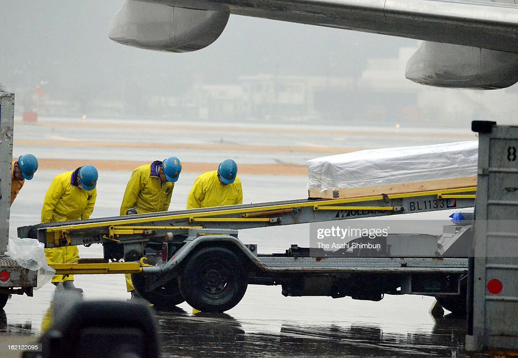Airport staffs bow as a container carrying the bodies of victim Hitoshi Yokota at Guam mass stabbing unloaded at Narita International Airport on February 18, 2013 in Narita, Chiba, Japan. A 21-year-old man was arrested for killing two visitors and injuring a dozen others after crashing his car and stabbing people.