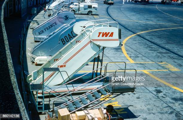 Airport tarmac with several portable aircraft boarding stairs for major airlines including Transworld Airlines Air France and British Overseas Airway...