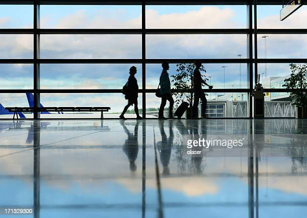 Airport terminal, travellers in silhouette