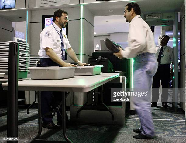 Airport travelers pass through Transportation Security Administration screeners May 26 2004 at the Miami International Airport in Miami Florida As...
