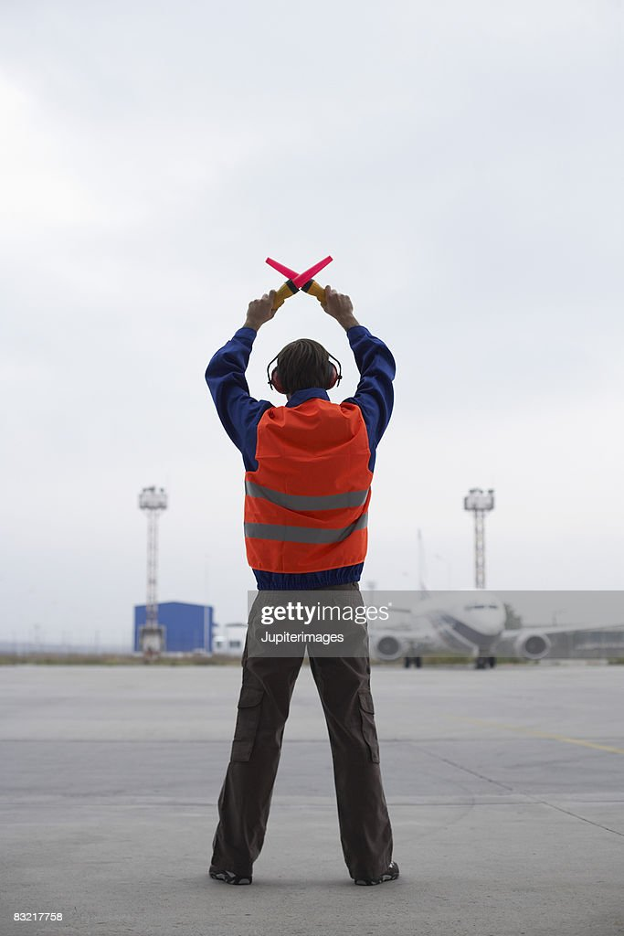 Airport worker directing airplane