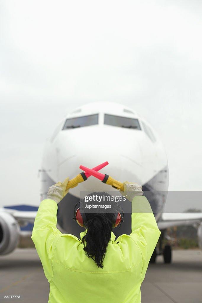 Airport worker directing jet