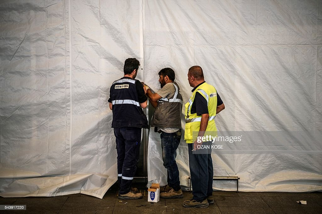 Airport workers cover broken windows with a tarpaulin at Ataturk airport international terminal on June 30, 2016, two days after a suicide bombing and gun attack targeted Istanbul's Ataturk airport, killing 42 people. Turkey today detained 13 suspected Islamic State jihadists over the deadly Istanbul airport attack, as chilling details emerged of how suicide bombers launched their assault. The death toll from Tuesday's gun and suicide bomb spree at Ataturk airport has risen to 44, state-run news agency Anadolu said, with more than 200 people injured. KOSE