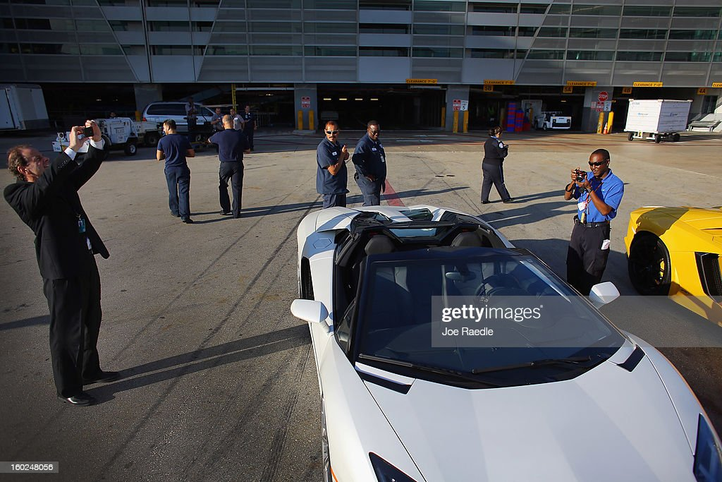 Airport workers look at the new Lamborghini Aventador LP700-4 Roadsters on the tarmac at the Miami International Airporton January 28, 2013 in Miami, Florida. The world wide unveiling of the new luxury super sports cars took place at the airport and included the vehicles being driven down the south runway of Miami International Airport.