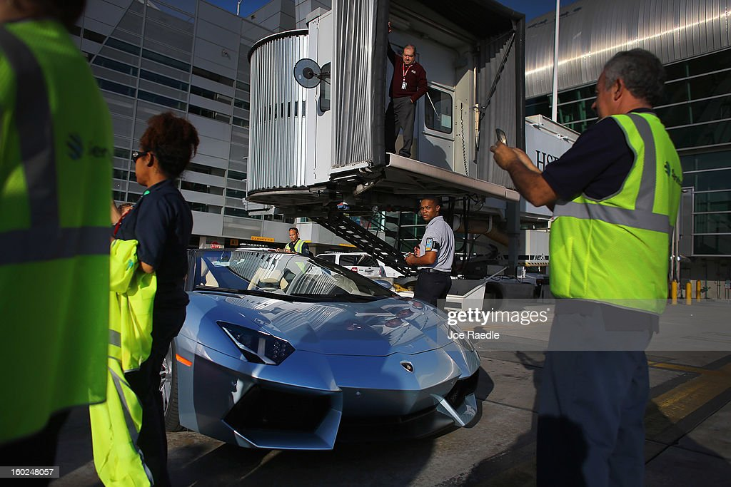 Airport workers look at the new Lamborghini Aventador LP700-4 Roadster on the tarmac at the Miami International Airporton January 28, 2013 in Miami, Florida. The world wide unveiling of the new luxury super sports cars took place at the airport and included the vehicles being driven down the south runway of Miami International Airport.