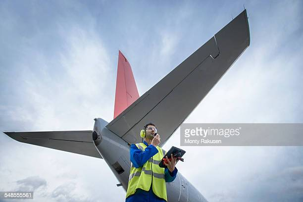 Airside engineer talking on radio near aircraft on runway, low angle view
