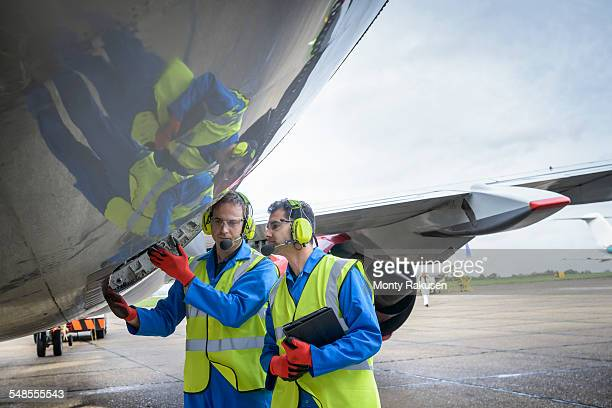 Airside engineers inspecting jet aircraft on runway