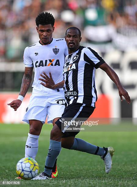 Airton of Botafogo struggles for the ball with Junior Urso of Atletico Mineiro during a match between Botafogo and Atletico Mineiro as part of...