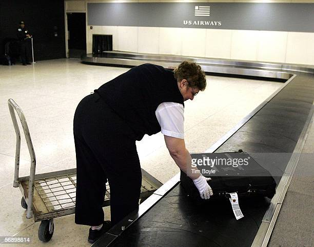 Airways customer service agent Raquel Cichy checks a yettobeclaimed piece of luggage at the US Airways luggage claim area February 21 2006 at O'Hare...