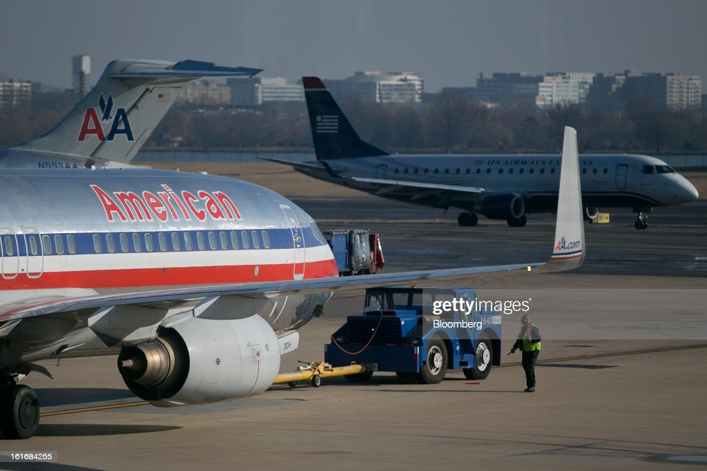Airways Group Inc. airplane, right, taxis near a AMR Corp.'s American Airlines airplane at Reagan National Airport in Washington, D.C., U.S., on Thursday, Feb. 14, 2013. US Airways Group Inc., spurned in three prior merger attempts, will combine with bankrupt AMR Corp.'s American Airlines in an $11 billion deal to create the world's largest carrier. Photographer: Andrew Harrer/Bloomberg via Getty Images