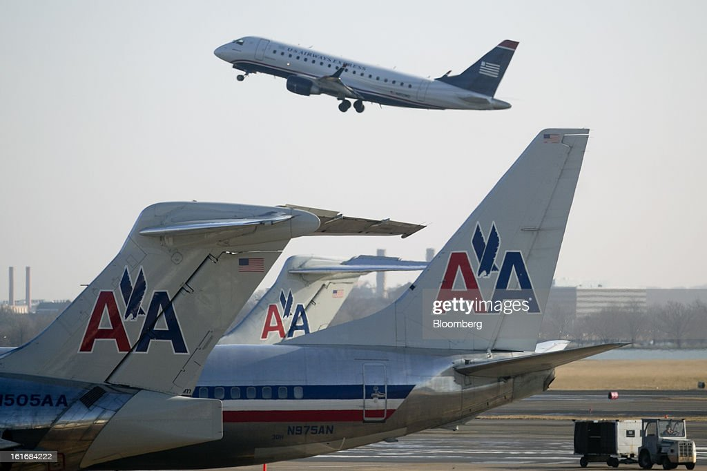 Airways Group Inc. airplane takes off behind AMR Corp.'s American Airlines airplanes at Reagan National Airport in Washington, D.C., U.S., on Thursday, Feb. 14, 2013. US Airways Group Inc., spurned in three prior merger attempts, will combine with bankrupt AMR Corp.'s American Airlines in an $11 billion deal to create the world's largest carrier. Photographer: Andrew Harrer/Bloomberg via Getty Images