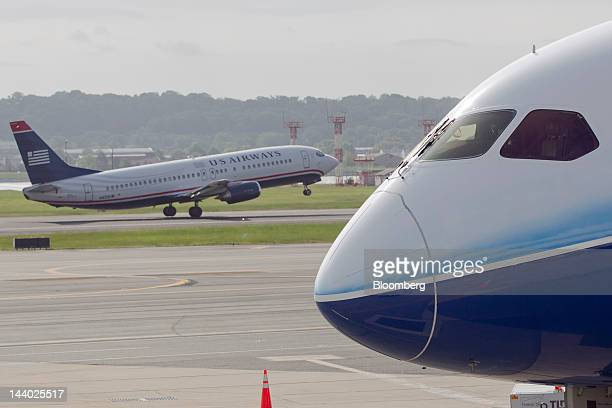 Airways Group Inc airplane takes off past a Boeing Co 787 Dreamliner on display during its global Dream Tour at Reagan National Airport in Washington...