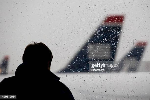 US Airways Group Inc airplanes sit on the tarmac past a traveler standing in front of a window at Ronald Reagan National Airport in Washington DC US...