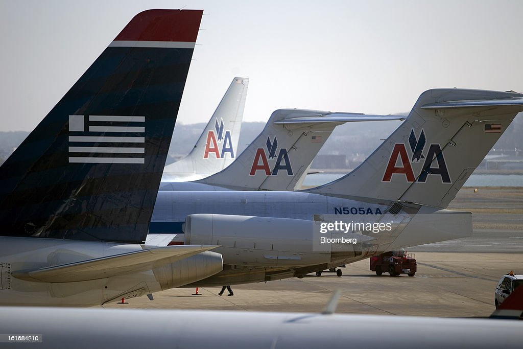 US Airways Group Inc. and AMR Corp.'s American Airlines airplanes sit parked on the tarmac at Reagan National Airport in Washington, D.C., U.S., on Thursday, Feb. 14, 2013. US Airways Group Inc., spurned in three prior merger attempts, will combine with bankrupt AMR Corp.'s American Airlines in an $11 billion deal to create the world's largest carrier. Photographer: Andrew Harrer/Bloomberg via Getty Images