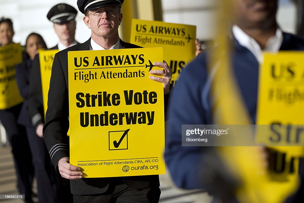Airways Group Inc. pilot and flight attendants picket at Reagan National Airport in Washington, D.C., U.S., on Wednesday, Nov. 14, 2012. 6,700 flight attendants, represented by the Association of Flight Attendants-CWA (AFA), are currently taking a strike vote to demonstrate what they are willing to do to achieve a contract that can be ratified. Photographer: Andrew Harrer/Bloomberg via Getty Images