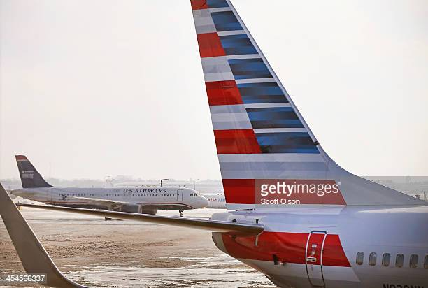 Airways jet passes an American Airlines jet with the company's new tail logo at O'Hare Airport on December 9 2013 in Chicago Illinois American...
