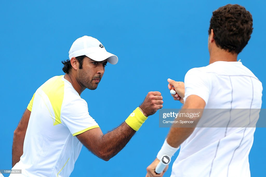Aisam-Ul-Haq Qureshi of Pakistan talks tactics with Jean-Julien Rojer of the Netherland in his second round doubles match against Xavier Malisse of Belgium and Dick Norman of Belgium during day five of the 2013 Australian Open at Melbourne Park on January 18, 2013 in Melbourne, Australia.