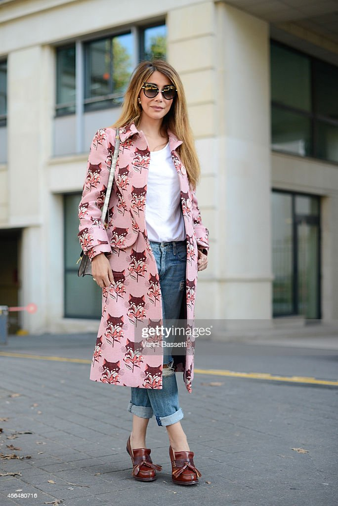Aisha Baker poses wearing a Miu Miu coat Current Elliot pants Acne shoes and Celine bag on the streets of Paris during Paris fashion week on October...