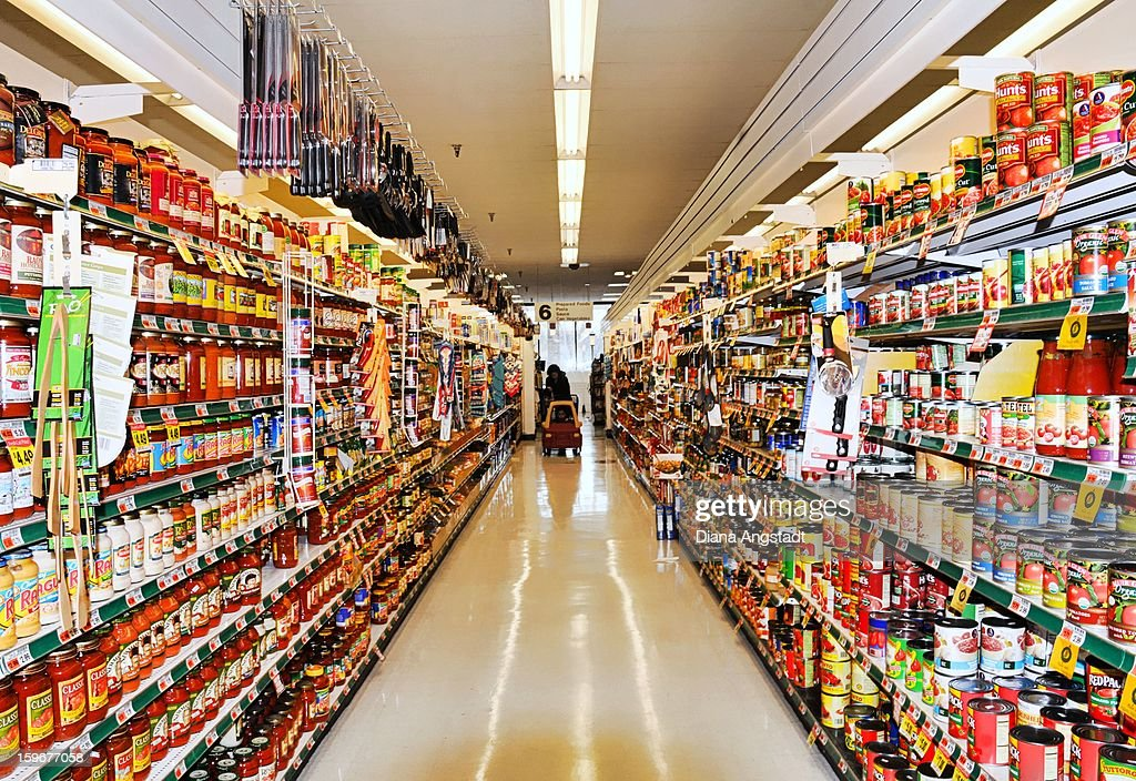 CONTENT] Aisle at supermarket with shopper and shopping cart