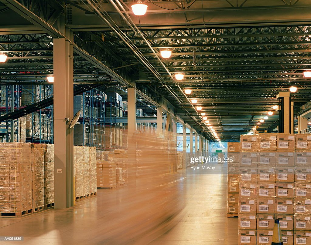 Aisle of warehouse, boxes stacked for distribution (blurred motion) : Stock Photo