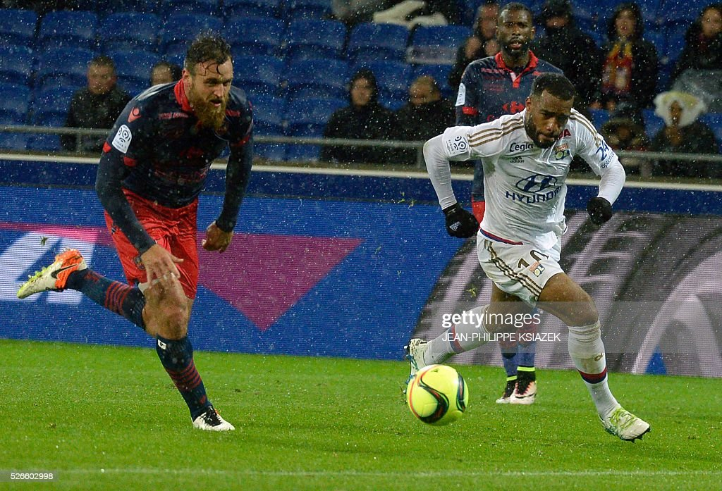 Ajaccio's French defender Roderic Filippi (L) vies withLyon's French forward Alexandre Lacazette (R) during the French L1 football match Lyon (OL) vs Ajaccio (GFCA) at the Parc Olympique Lyonnais stadium in Decines-Charpieu, central eastern France, on April 30, 2016.