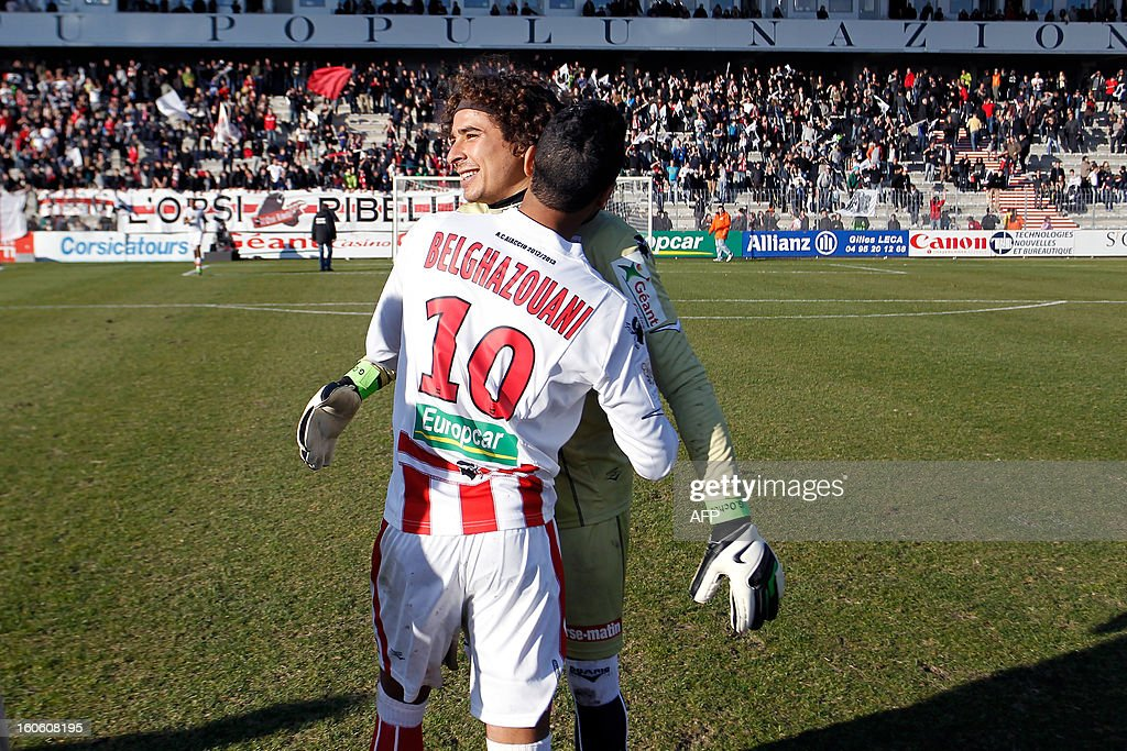 Ajaccio's Mexican goalkeeper Guillermo Ochoa is congratulated by Franco-Moroccan midfielder Chahir Belghazouani after winning the French L1 football match Ajaccio (ACA) vs Lyon (OL) in the Francois Coty stadium in Ajaccio, French Mediterranean island of Corsica, on February 3, 2013. Ajaccio won 3-1. AFP PHOTO / PASCAL POCHARD-CASABIANCA