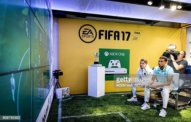 Ajax Amsterdam players Koen Weijland and Jairo Riedewald play a game on an 'Xbox One' during the opening of the FIFA 17 Xperience in Amsterdam on...