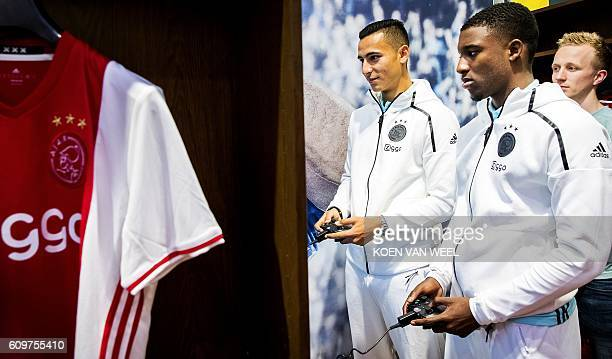 Ajax Amsterdam players Riechedly Bazoer and Anwar Al Ghazi play a game on an 'Xbox One' during the opening of the FIFA 17 Xperience in Amsterdam on...