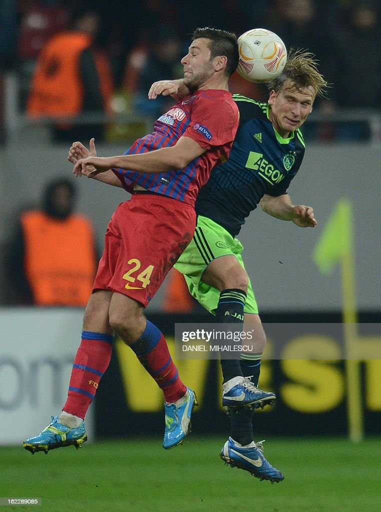 Ajax Amsterdam's Danish midfielder Christian Poulsen (R) vies for the ball with Bucharest's striker Raul Rusescu during the UEFA Europa League Round of 32 football match FC Steaua Bucuresti vs AFC Ajax in Bucharest, Romania on February 21, 2013.