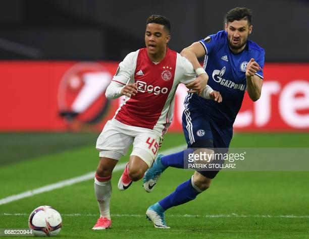Ajax Amsterdam's dutch striker Justin Kluivert and Schalke's Italian defender Daniel Caligiuri vie for the ball during the UEFA Europa League...