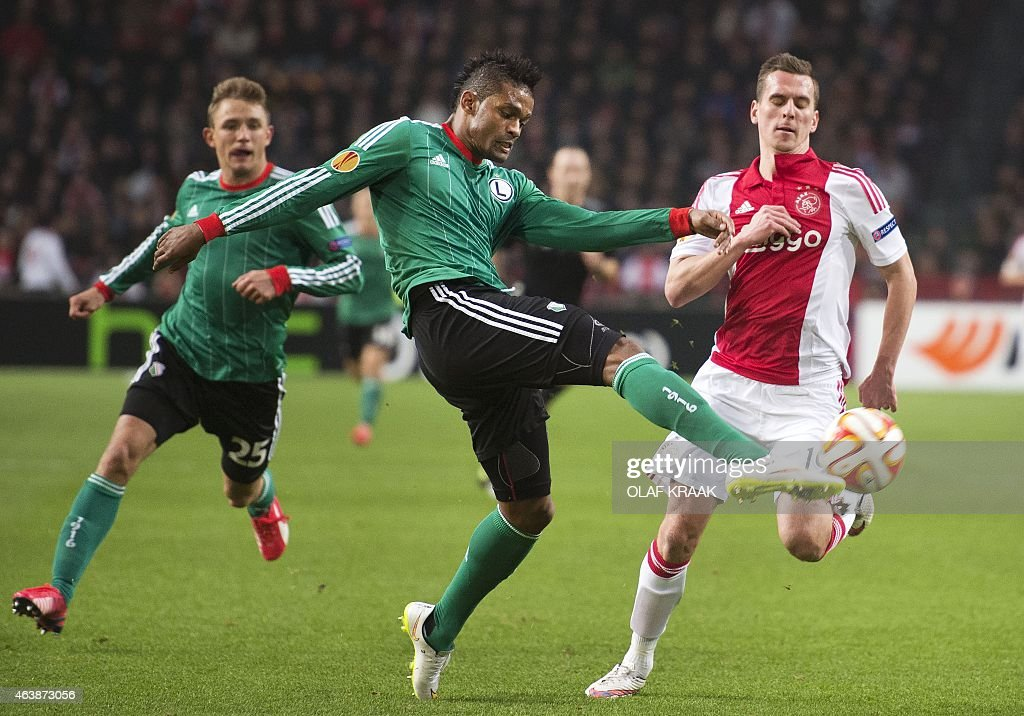 Ajax Amsterdam's Polish forward Arek Milik vies with Legia Warsaw's Cypriot defender Dosa Junior during their Europa League round of 32 first leg...
