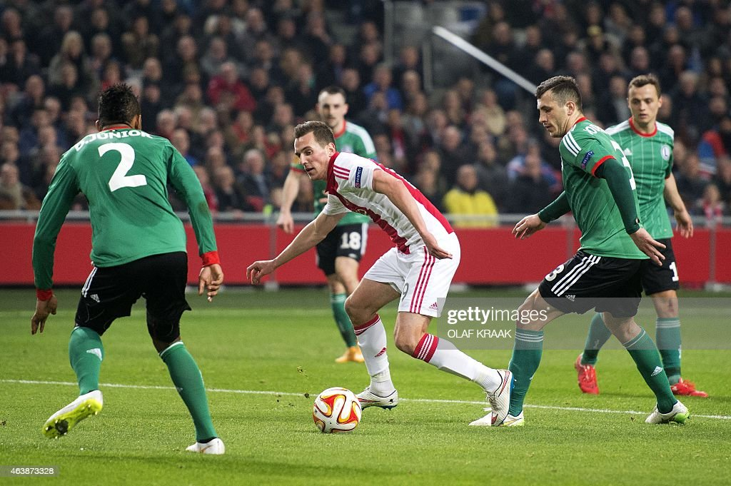 Ajax Amsterdam's Polish forward Arek Milik (C) vies with Legia Warsaw's Cypriot defender Dosa Junior (L) and Legia Warsaw's Polish defender <a gi-track='captionPersonalityLinkClicked' href=/galleries/search?phrase=Tomasz+Jodlowiec&family=editorial&specificpeople=5700915 ng-click='$event.stopPropagation()'>Tomasz Jodlowiec</a> during their Europa League round of 32 first leg football match at the Amsterdam Arena, on February 19, 2015. AFP PHOTO / ANP / OLAF KRAAK ** netherlands out **