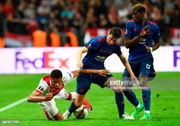 Ajax Brazilian forward David Neres Manchester United's Italian defender Matteo Darmian and Manchester United's French midfielder Paul Pogba vie for...