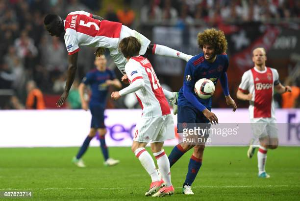 Ajax Colombian defender Davinson Sánchez jumps over Ajax Danish Midfielder Lasse Schone and Manchester United's Belgian midfielder Marouane Fellaini...