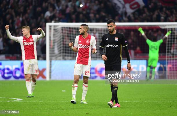 Ajax defender Matthijs de Ligt Ajax midfielder Hakim Ziyech celebrate the victory as Lyon's French Algerian midfielder Rachid Ghezzal leavse the...