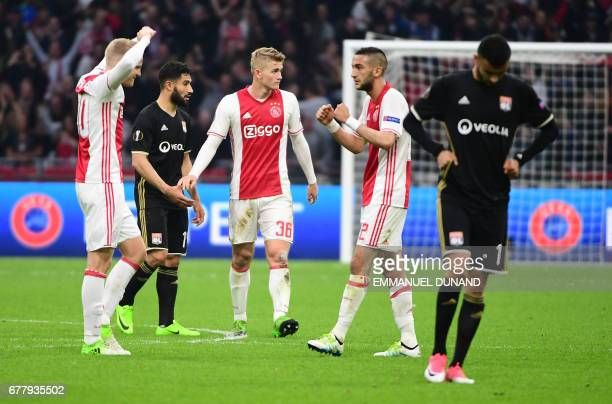 Ajax defender Matthijs de Ligt Ajax midfielder Hakim Ziyech celebrate the victory as Lyon's French Algerian midfielder Rachid Ghezzal leaves the...