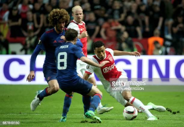 Ajax Dutch defender Jairo Riedewald vies for the ball with Manchester United's Belgian midfielder Marouane Fellaini and Manchester United's Spanish...