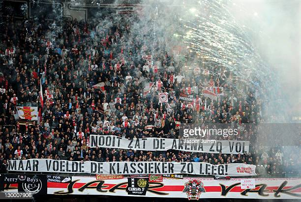 Ajax fans cheer as fireworks are lit holding a banner reading 'The Arena was never this full with the Klassieker feeling so empty' refering to the...