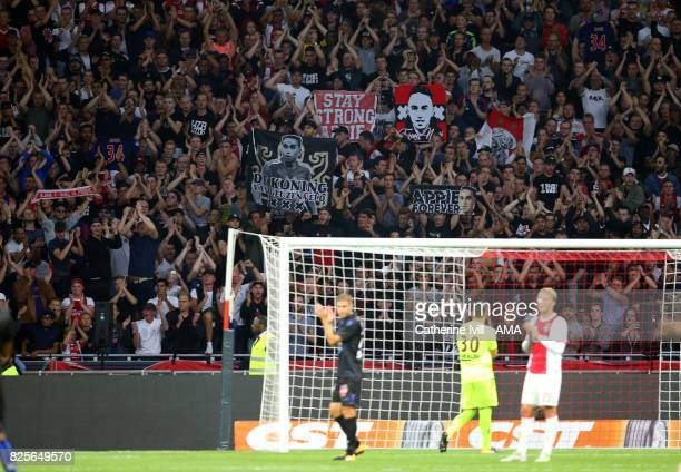 Ajax fans hold up signs in support of Abdelhak Nouri of Ajax as both players and fans applaud in the 34th minute during the UEFA Champions League...