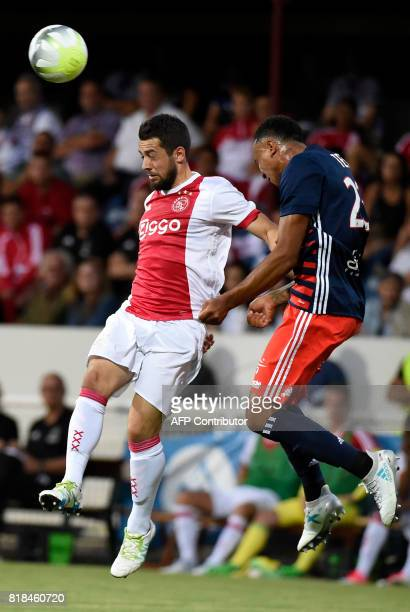 Ajax forward Amin Younes and Lyon's Dutch defender Kenny Tete go for a header during a friendly football match between Olympique Lyonnais and Ajax...