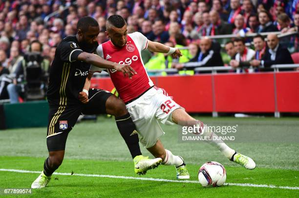 Ajax midfielder Hakim Ziyech vies with Lyon's French Cameroonian defender Nicolas Nkoulou during UEFA Europa League semifinal first leg Ajax...