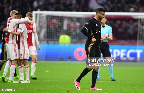 Ajax players celebrate the victory as Lyon's French Algerian midfielder Rachid Ghezzal leaves the pitch after UEFA Europa League semifinal first leg...