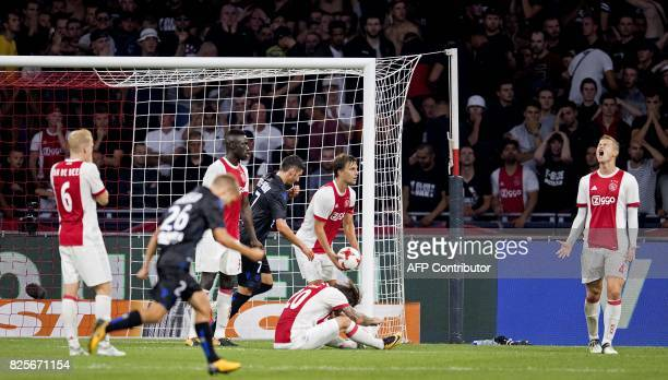 Ajax players react after Nice's player Vincent Marcel scored an equalizer during the Champions League second leg football match between OGC Nice and...