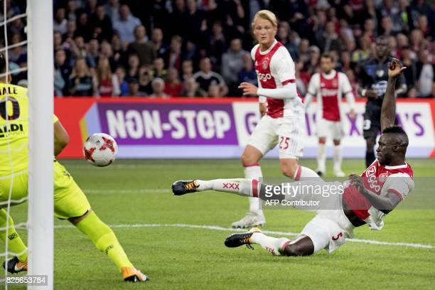 Ajax's defender Davinson Sanchez is watched by teammate Kasper Dolberg as he scores during the Champions League second leg football match between OGC...