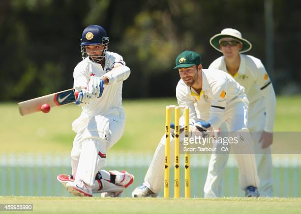 Ajinkya Rahane of India hits a boundary as wicketkeeper Seb Gotch of the Cricket Australia XI looks on during the international tour match between...