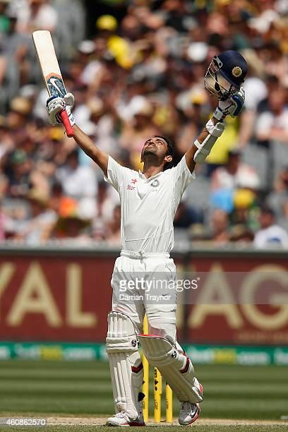 Ajinkya Rahane of India raises his bat after scoring 100 runs during day three of the Third Test match between Australia and India at Melbourne...