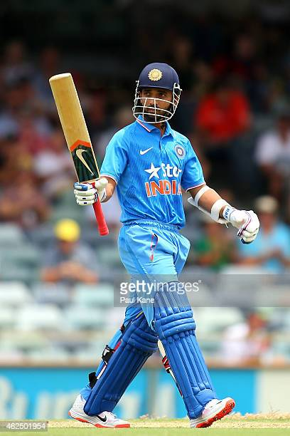 Ajinkya Rahane of India raises his bat to celebrate his half century during the One Day International match between England and India at the WACA on...