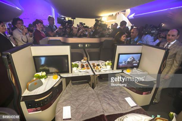 Akbar Al Baker chief executive officer of Qatar Airways Ltd far right speaks to members of the media during the unveiling of the airline's new...